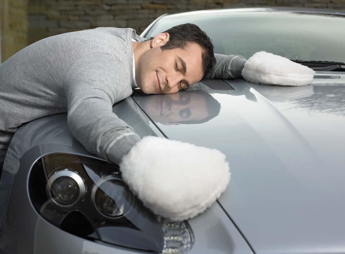 Мужчина лежит на капоте автомобиля в белых варежках для полировки